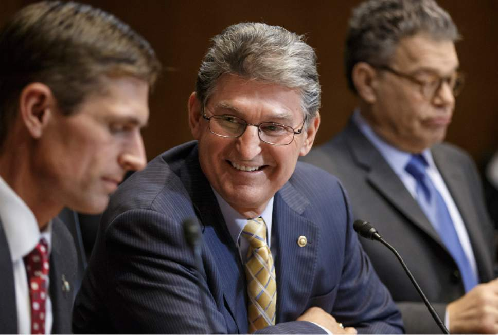 Sen. Joe Manchin, D-W.V., a Democratic sponsor of the long-stalled Keystone XL pipeline bill, flanked by Sen. Al Franken, D-Minn., right, and Sen. Martin Heinrich, D-N.M., left, smiles after the 13-9 vote in the Senate Energy and Natural Resources Committee that moves the bill closer to the floor, Thursday, Jan. 8, 2015, on Capitol Hill in Washington. As promised by Republican leaders who now hold the majority in Congress, the Keystone bill is at the top of their agenda after it fell short of passage in December when Democrats ruled the Senate. (AP Photo/J. Scott Applewhite)
