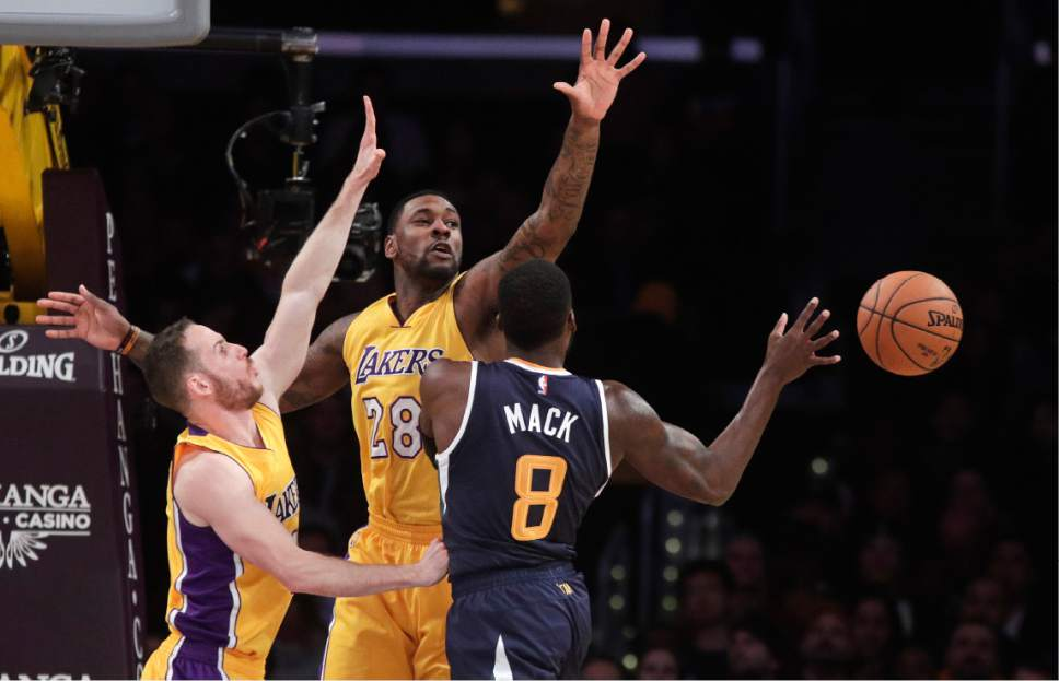Utah Jazz's Shelvin Mack, center, passes the ball as he is defended by Los Angeles Lakers' Marcelo Huertas, left, and Tarik Black during the first half of an NBA basketball game, Monday, Dec. 5, 2016, in Los Angeles. (AP Photo/Jae C. Hong)