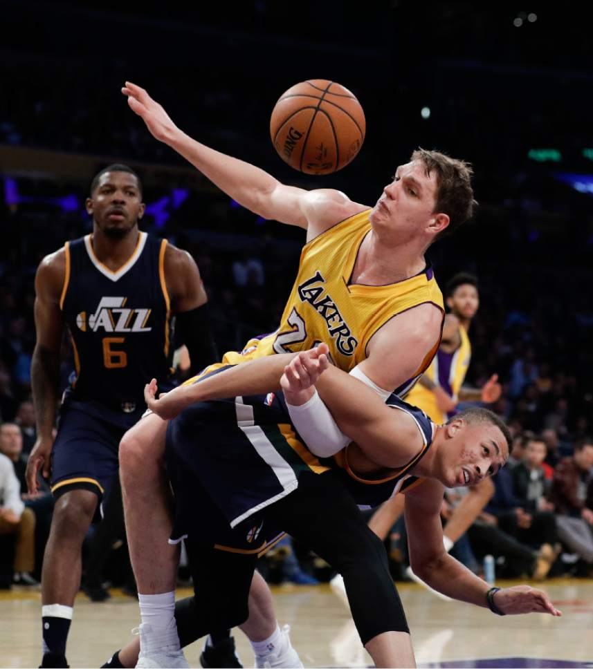 Los Angeles Lakers' Timofey Mozgov, top, of Russia, and Utah Jazz's Dante Exum are tangled up during the first half of an NBA basketball game, Monday, Dec. 5, 2016, in Los Angeles. (AP Photo/Jae C. Hong)