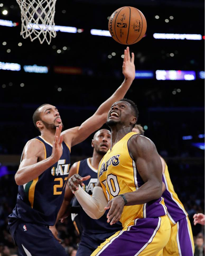 Los Angeles Lakers' Julius Randle, front, and Utah Jazz's Rudy Gobert look at the ball during the first half of an NBA basketball game, Monday, Dec. 5, 2016, in Los Angeles. (AP Photo/Jae C. Hong)