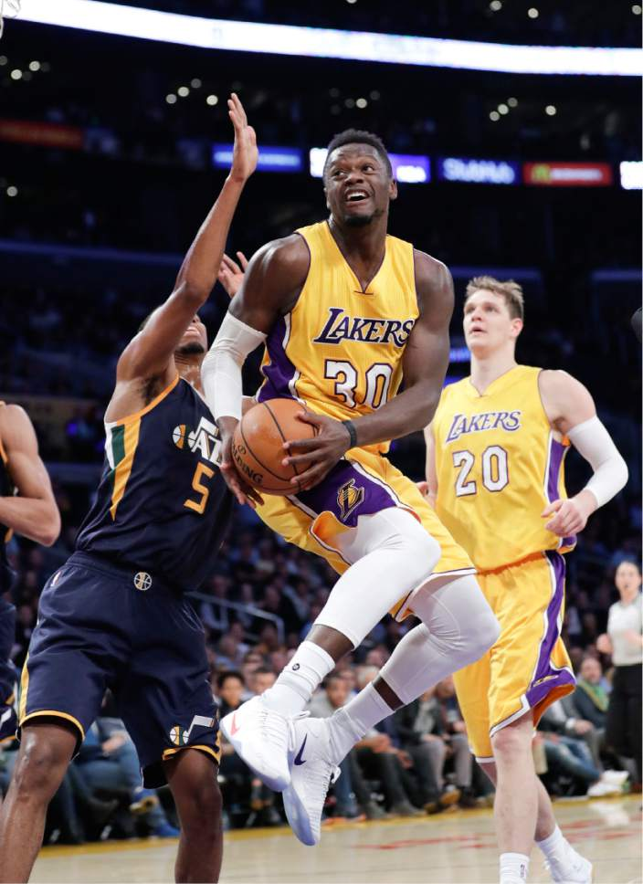 Los Angeles Lakers' Julius Randle goes up for a basket past Utah Jazz's Rodney Hood during the first half of an NBA basketball game, Monday, Dec. 5, 2016, in Los Angeles. (AP Photo/Jae C. Hong)