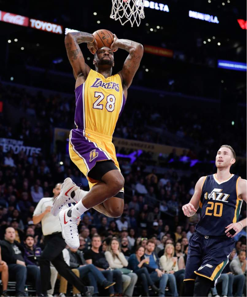Los Angeles Lakers' Tarik Black, left, goes up for a dunk as Utah Jazz's Gordon Hayward watches during the first half of an NBA basketball game, Monday, Dec. 5, 2016, in Los Angeles. (AP Photo/Jae C. Hong)
