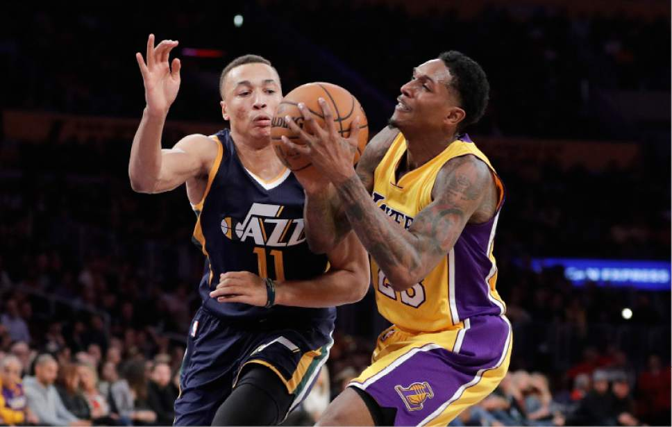 Los Angeles Lakers' Louis Williams, right, is defended by Utah Jazz's Dante Exum during the first half of an NBA basketball game, Monday, Dec. 5, 2016, in Los Angeles. (AP Photo/Jae C. Hong)