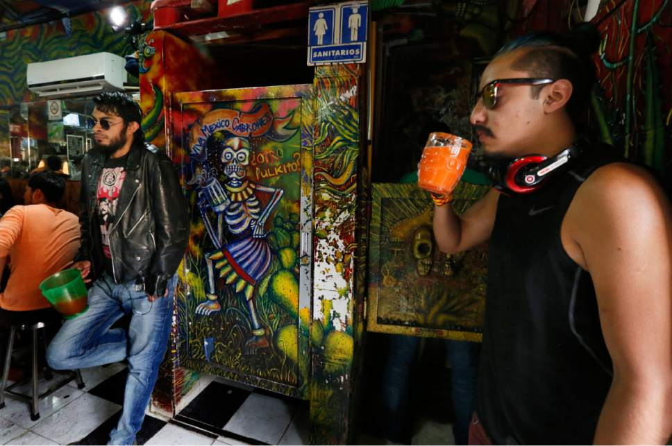 In this Dec. 3, 2016 photo, patrons sip from containers filled with pulque at Las Duelistas pulqueria, in Mexico City. The nutrient-rich drink is making a comeback among a new generation of Mexicans. (AP Photo/Marco Ugarte)
