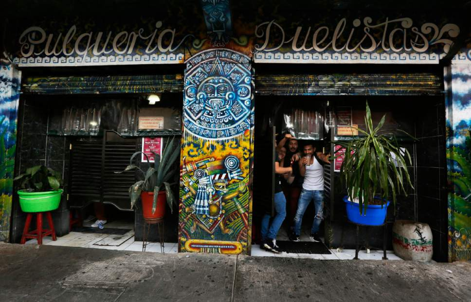 In this Dec. 3, 2016 photo, patrons stand in a doorway of Las Duelistas pulqueria, in Mexico City. Artisanal producers complain that tax codes, health codes and commercial requirements have conspired to keep their pulque businesses small. (AP Photo/Marco Ugarte)
