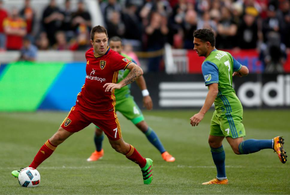 Real Salt Lake's Juan Manuel Martinez, left, looks to pass the ball past Seattle Sounders' Cristian Roldan (7) during the first half of an MLS soccer game on Saturday, March 12, 2016, in Sandy, Utah.  (AP Photo/Kim Raff)