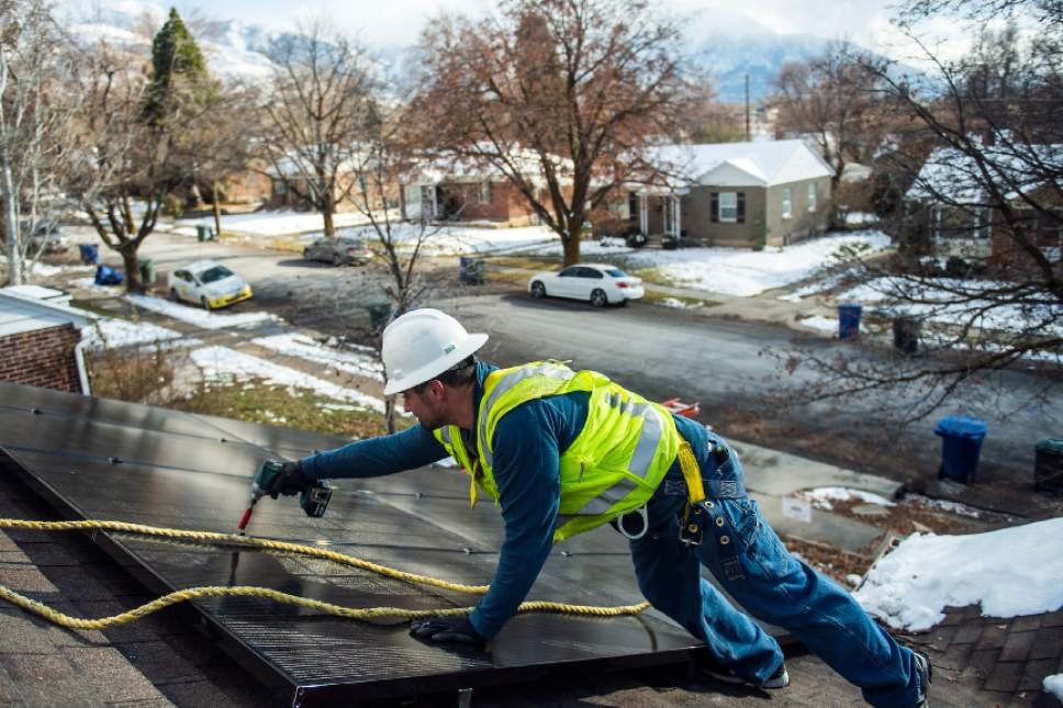 Chris Detrick  |  The Salt Lake Tribune Creative Energies lead electrician Justin Therrien installs solar panels on top of a home in Salt Lake City Wednesday December 7, 2016.