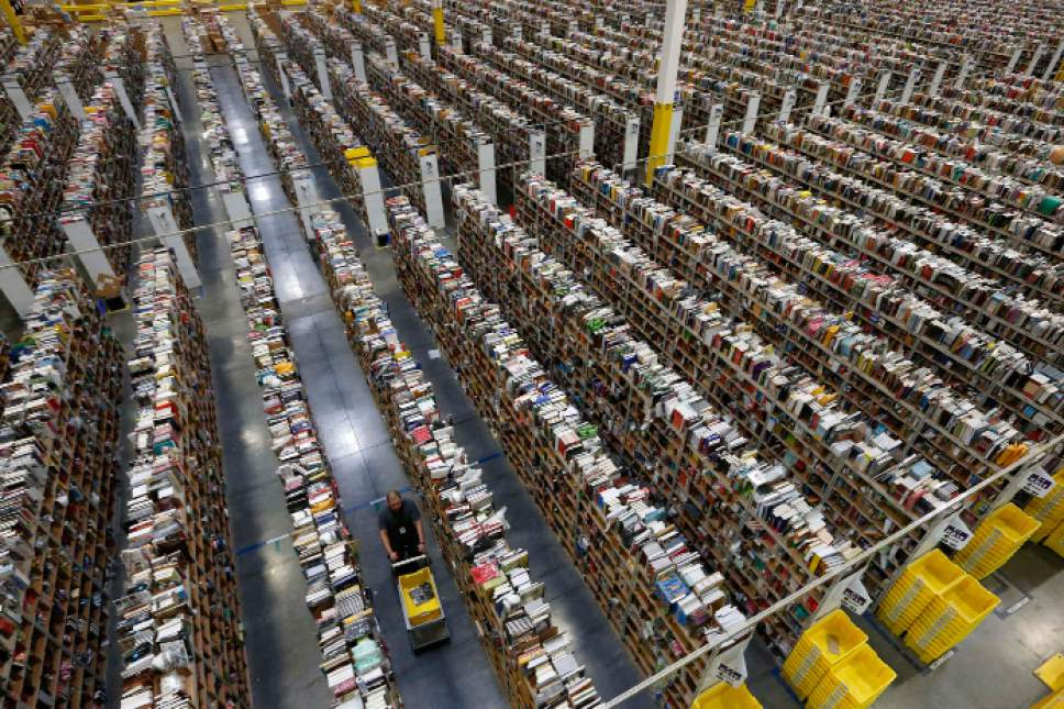 FILE - In this Dec. 2, 2013 file photo, an Amazon employee walks down one of the miles of aisles at the company's fulfillment center in Phoenix. Amazon launched at the dawn of the Web as an online bookseller on July 16, 1995. (AP Photo/Ross D. Franklin, File)