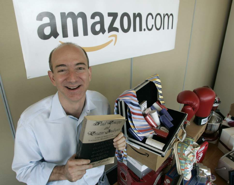 "FILE - In this June 17, 2005 file photo, Amazon.com founder and CEO Jeff Bezos holds a copy of ""Fluid Concepts and Creative Analogies"" by Douglas Hofstadter -- the first book sold online by Amazon.com -- as he poses for photos at the company's headquarters in Seattle. Amazon launched at the dawn of the Web as an online bookseller on July 16, 1995. (AP Photo/Ted S. Warren, File)"