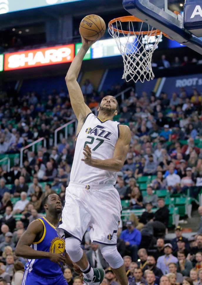 Utah Jazz center Rudy Gobert (27) dunks as Golden State Warriors forward Draymond Green (23) looks on in the second half during an NBA basketball game Thursday, Dec. 8, 2016, in Salt Lake City. The Warriors won 106-99. (AP Photo/Rick Bowmer)
