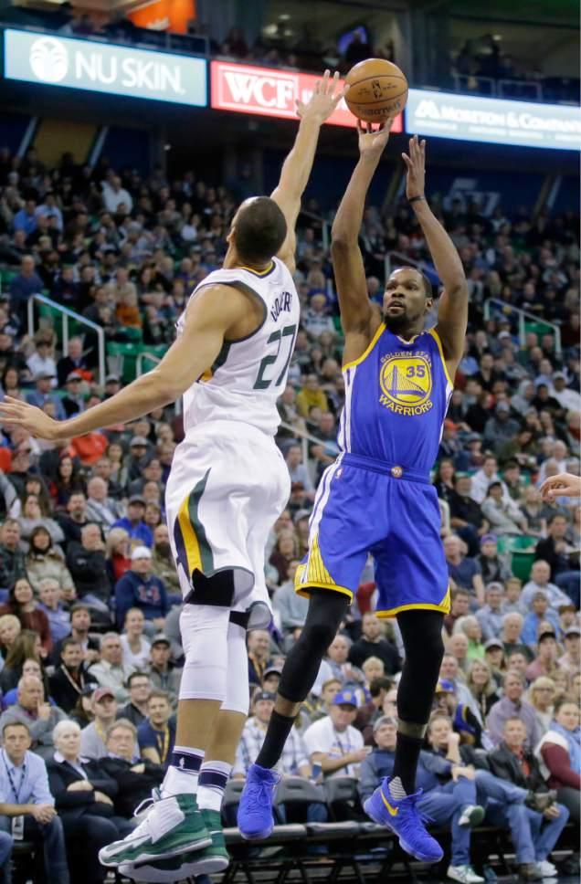 Golden State Warriors forward Kevin Durant (35) shoots as Utah Jazz center Rudy Gobert (27) defends in the first half during an NBA basketball game Thursday, Dec. 8, 2016, in Salt Lake City. (AP Photo/Rick Bowmer)