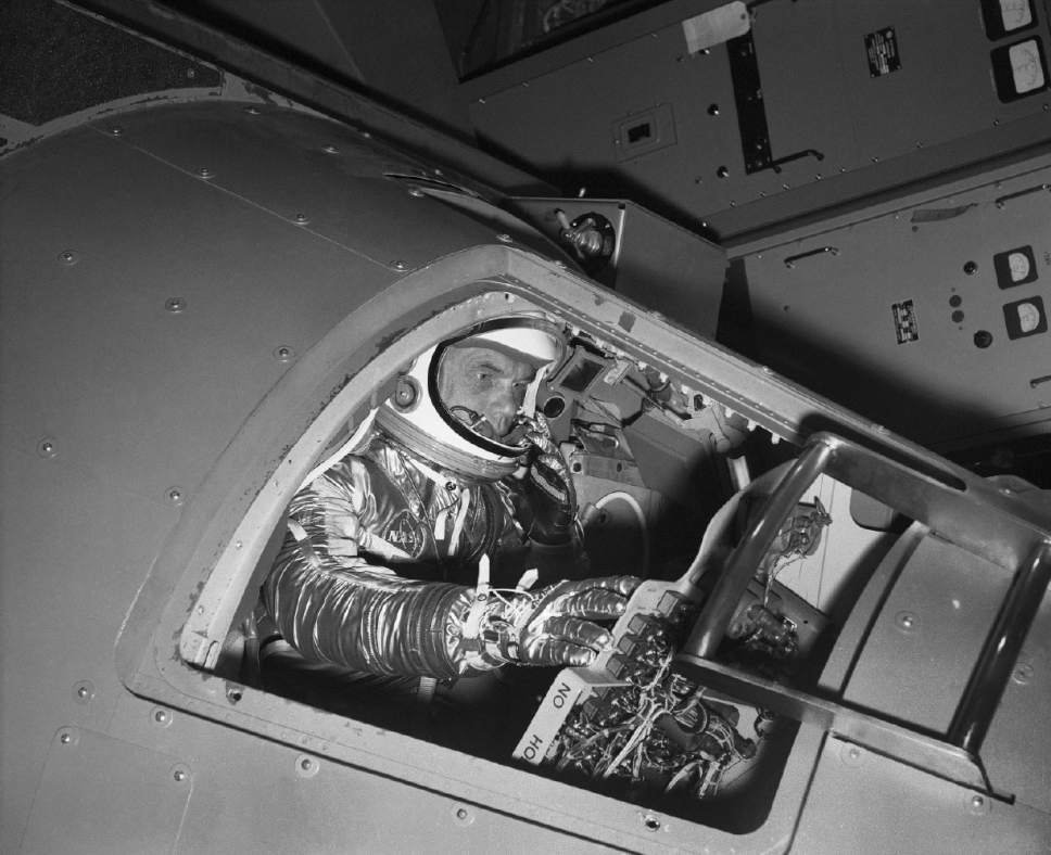 FILE - In this Jan. 11, 1961 file photo, Marine Lt. Col. John Glenn reaches for controls inside a Mercury capsule procedures trainer as he shows how the first U.S. astronaut will ride through space during a demonstration at the National Aeronautics and Space Administration Research Center in Langley Field, Va. Glenn, the first American to orbit Earth who later spent 24 years representing Ohio in the Senate, died Thursday, Dec. 8, 2016, at the age of 95. (AP Photo/File)