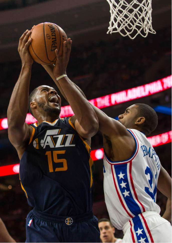 Utah Jazz's Derrick Favors, left, goes up for the shot with Philadelphia 76ers' Hollis Thompson, right, defending during the second half of an NBA basketball game, Monday, Nov. 7, 2016, in Philadelphia. The Jazz won 109-84. (AP Photo/Chris Szagola)