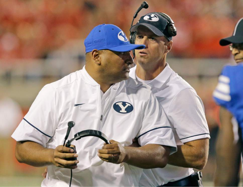 In this Sept. 10, 2016, photo, BYU assistant coach Ed Lamb, right, holds head coach Kalani Sitake as he reacts to a call from a referee in the second half during an NCAA college football game against Utah, in Salt Lake City.  (AP Photo/Rick Bowmer)