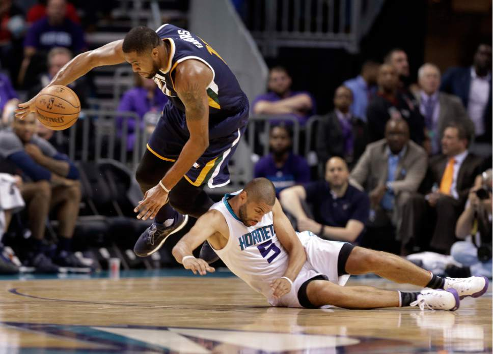 Utah Jazz's Derrick Favors, top, collides with Charlotte Hornets' Nicolas Batum as they chase a loose ball during the second half of an NBA basketball game in Charlotte, N.C., Wednesday, Nov. 9, 2016. The Hornets won 104-98. (AP Photo/Chuck Burton)