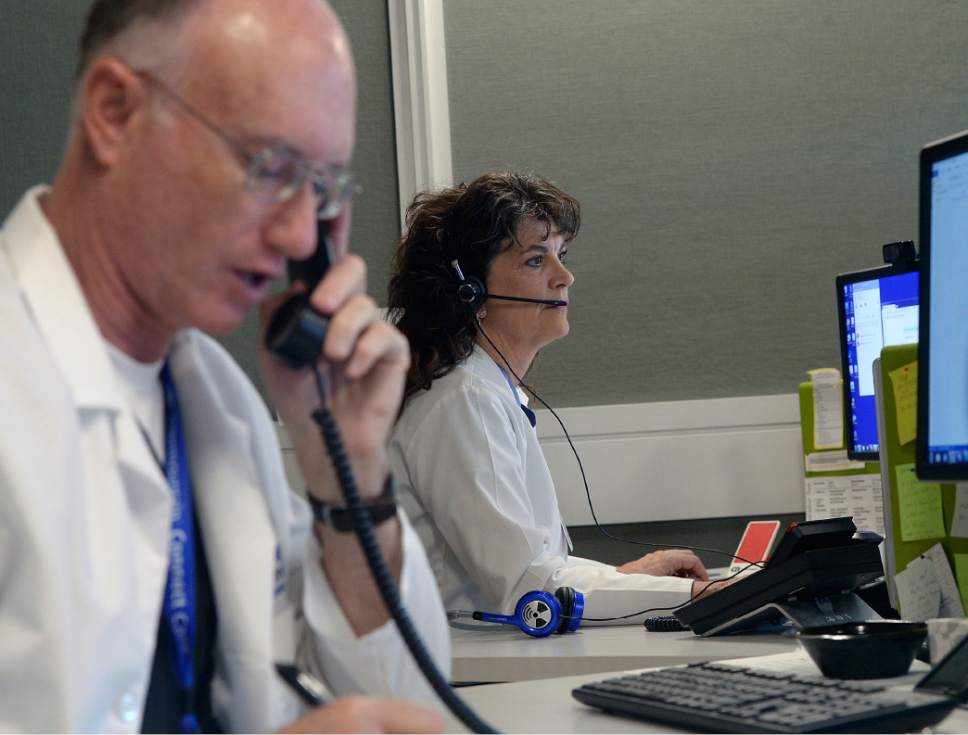 Al Hartmann  |  The Salt Lake Tribune Physician Assistants Wayne Crawford and Robin Dale talk to patients by teleconference at Intermountain Supply Chain Center in Midvale Monday Dec. 12.  Patients can call in with an ailment and symptoms.  The patients medical records and history are available for the doctors to diagnose and order medications.