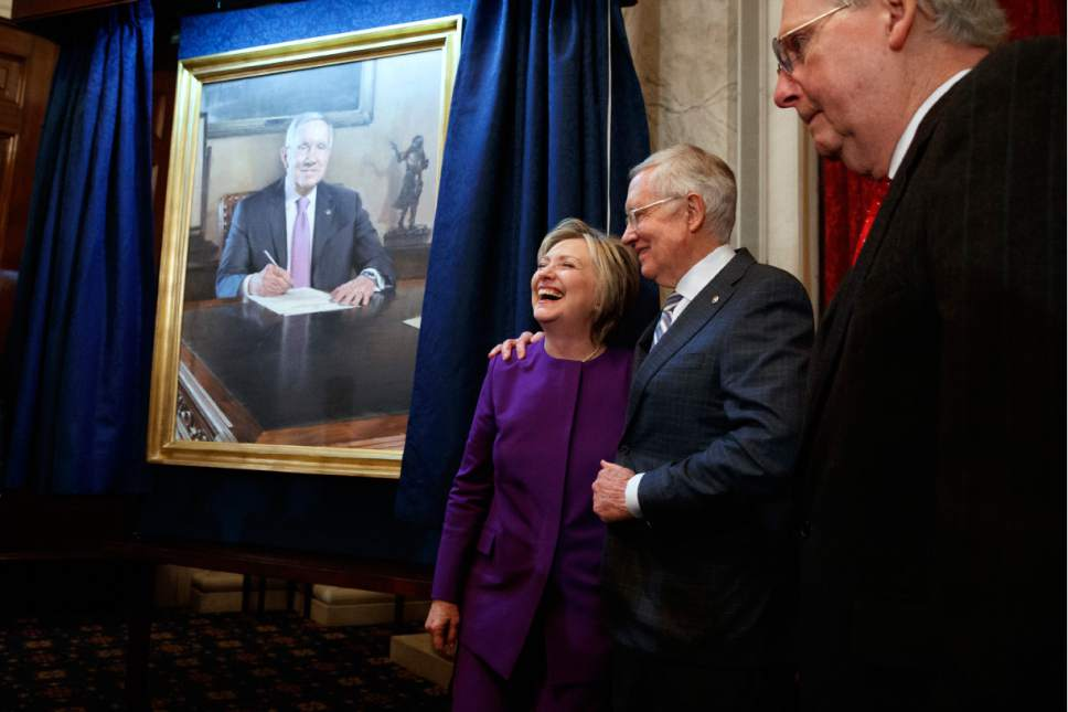 Senate Majority Leader Sen. Mitch McConnell, R-Ky., right, watches as Senate Minority Leader Sen Harry Reid, D-Nev., hugs Hillary Clinton during a ceremony to unveil a portrait of Reid, on Capitol Hill, Thursday, Dec. 8, 2016, in Washington. (AP Photo/Evan Vucci)