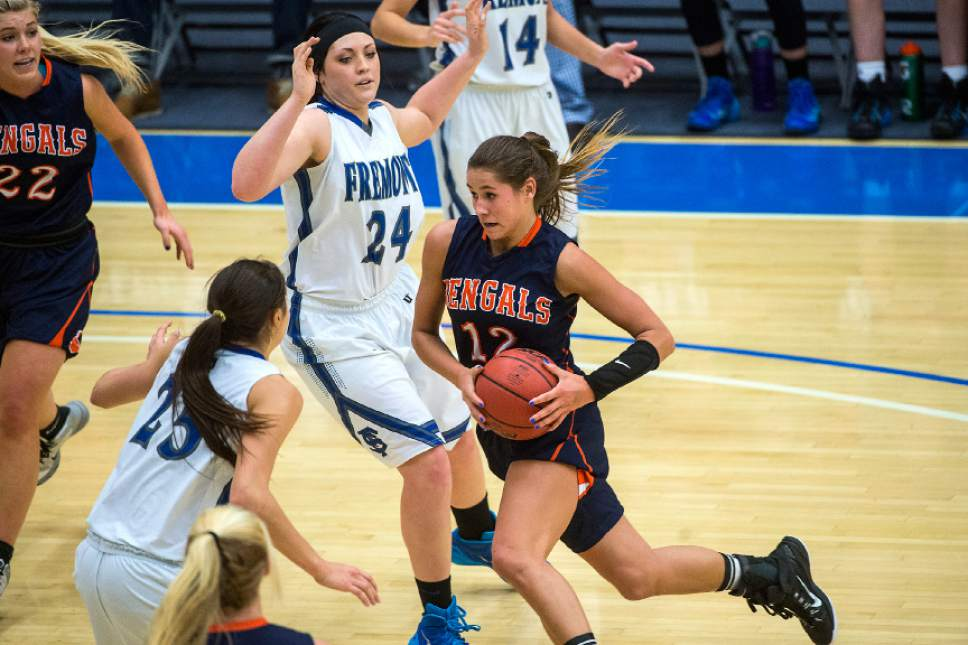 Chris Detrick  |  The Salt Lake Tribune Brighton's Dani Barton (12) runs past Fremont's Maryah Tipping (25) and Fremont's Rylee Thompson (24) during the 5A State Championship game at Salt Lake Community College Lifetime Activities Center Saturday February 21, 2015.  Brighton won the game 49-40.