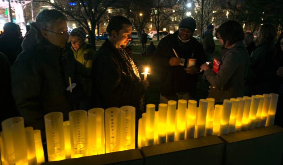 "Steve Griffin / The Salt Lake Tribune   People light candles during the ""Homeless Persons Memorial Day"" gathering for all the homeless people who died in the past year, at Pioneer Park in Salt Lake City Tuesday December 13, 2016."
