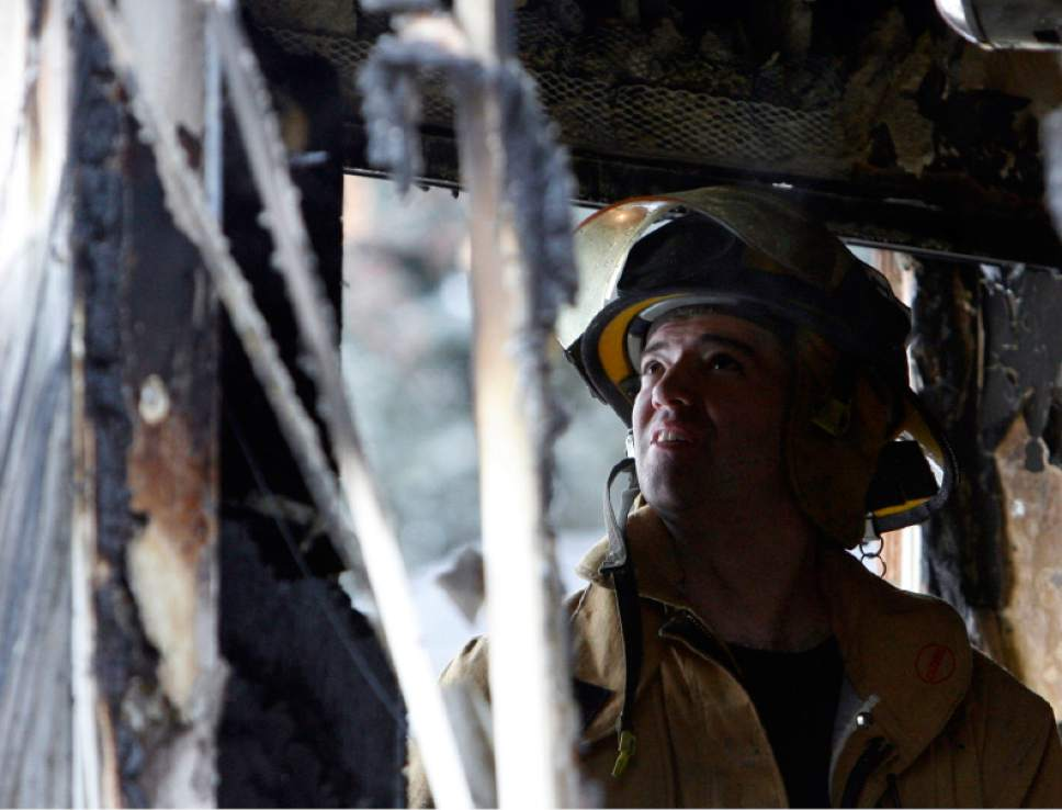 Jim Urquhart  |  Tribune File Photo  Unified Fire Department firefighter and paramedic Jay Stevens investigates the scene of a residential fire at 2445 E. 3646 South.