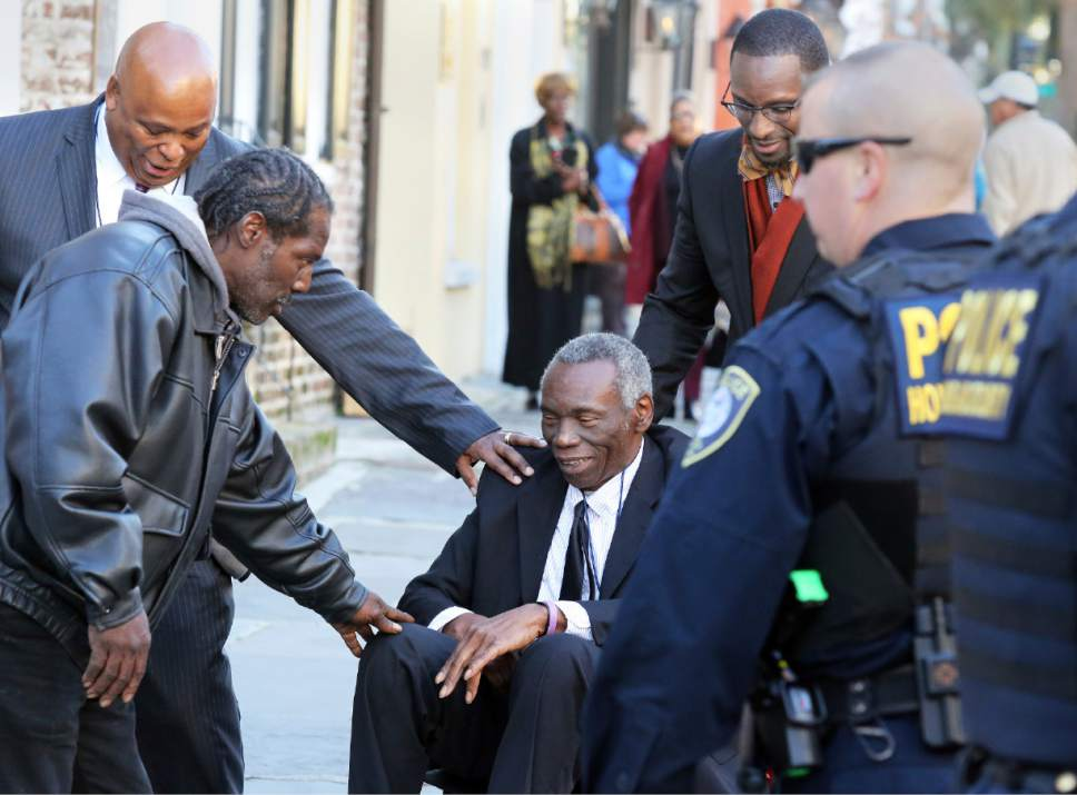 John Pinckney, father of shooting victim Rev. Clementa Pinckney, is greeted after leaving J. Waites Waring Federal Courthouse in Charleston, S.C., Thursday, Dec. 15, 2016, where Dylan Roof was found guilty of all 33 federal charges in the Emanuel AME Church shootings. (Brad Nettles/The Post And Courier via AP)