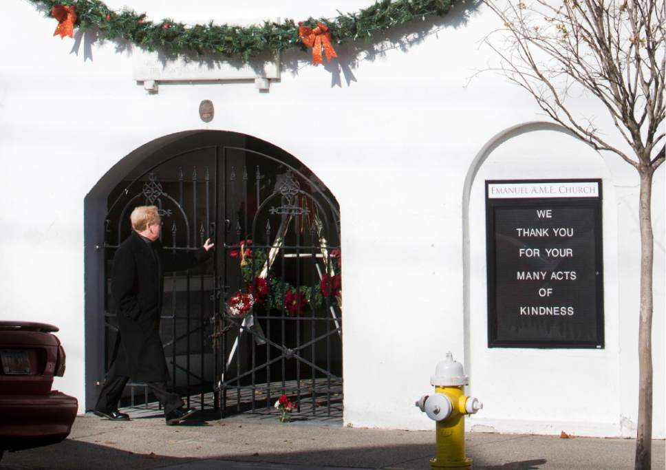 A man walks past flowers and a wreath at a door of Emanuel A.M.E. Church on Thursday, Dec. 15, 2016. Dylann Roof was convicted Thursday in the slaughter of nine black church members who had welcomed him to their Bible study at the church, a devastating crime in a country that was already deeply embroiled in racial tension. (Michael Pronzato/The Post And Courier via AP)