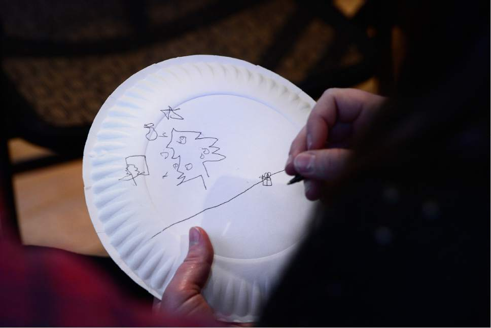 "Scott Sommerdorf   |  The Salt Lake Tribune   As one of the activities at Sunday Assembly Salt Lake City, people were asked to do ""the paper plate challenge"" - a blind drawing game, where they drew a Christmas tree, presents, a fireplace and stockings on a plate placed on top of their heads, Sunday, December 9, 2016."