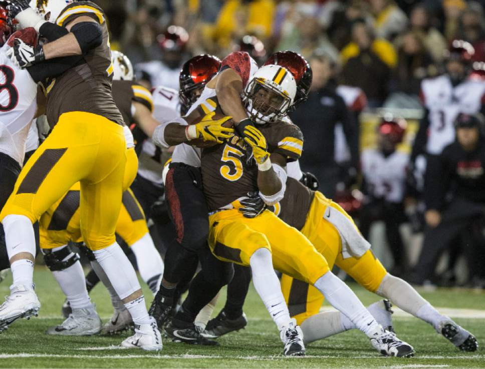 Wyoming's Brian Hill is tackled by San Diego State defenders during the first half of an NCAA college football game, Saturday, Dec. 3, 2016, in Laramie, Wyo. (AP Photo/Michael Smith)