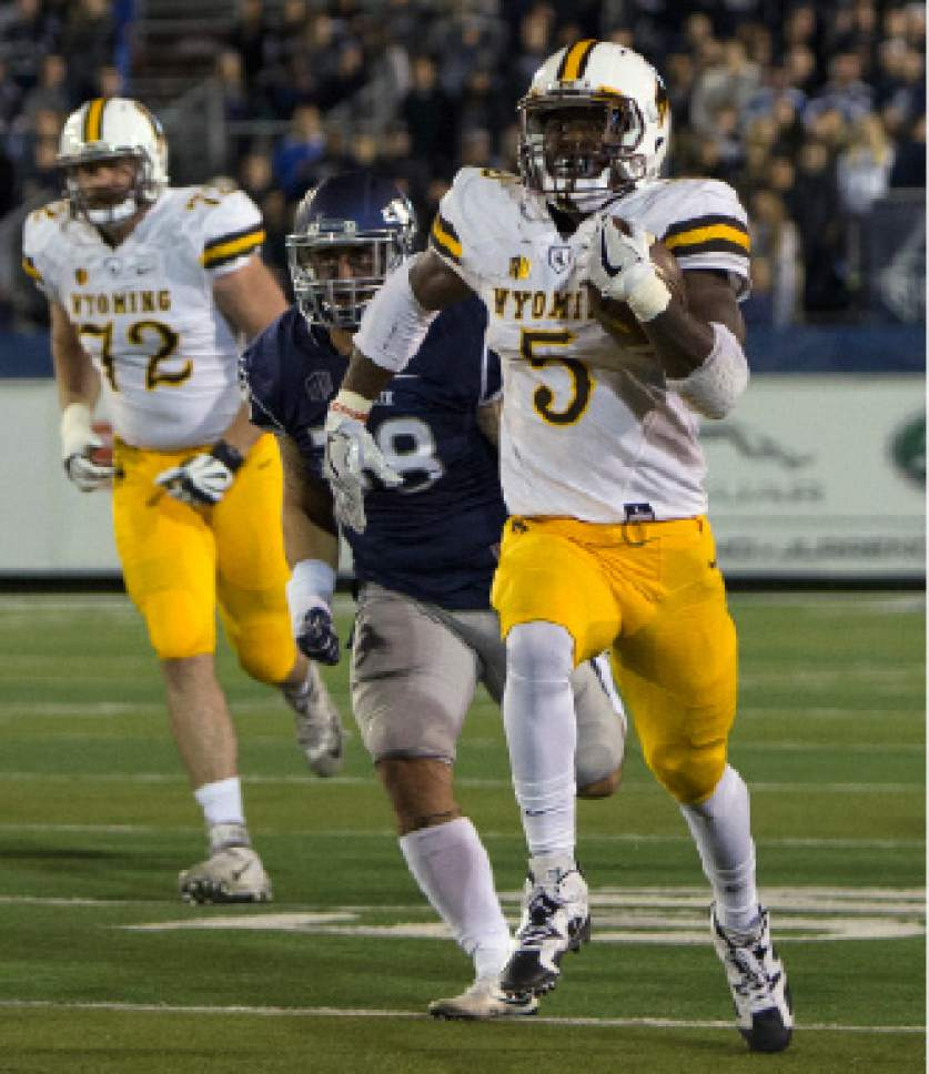 """FILE - In this Oct. 22, 2016, file photo, Wyoming running back Brian Hill runs for a touchdown against Nevada in the first half of an NCAA college football game, in Reno, Nev. A week ago before their final regular season games, both San Diego State and Wyoming knew they would be playing this weekend for the Mountain West Conference championship. And both teams looked bad in big losses. """"So we're both coming from the same situation and whichever team rebounds the best is going to win it,"""" Aztecs coach Rocky Long said.(AP Photo/Tom R. Smedes, File)"""