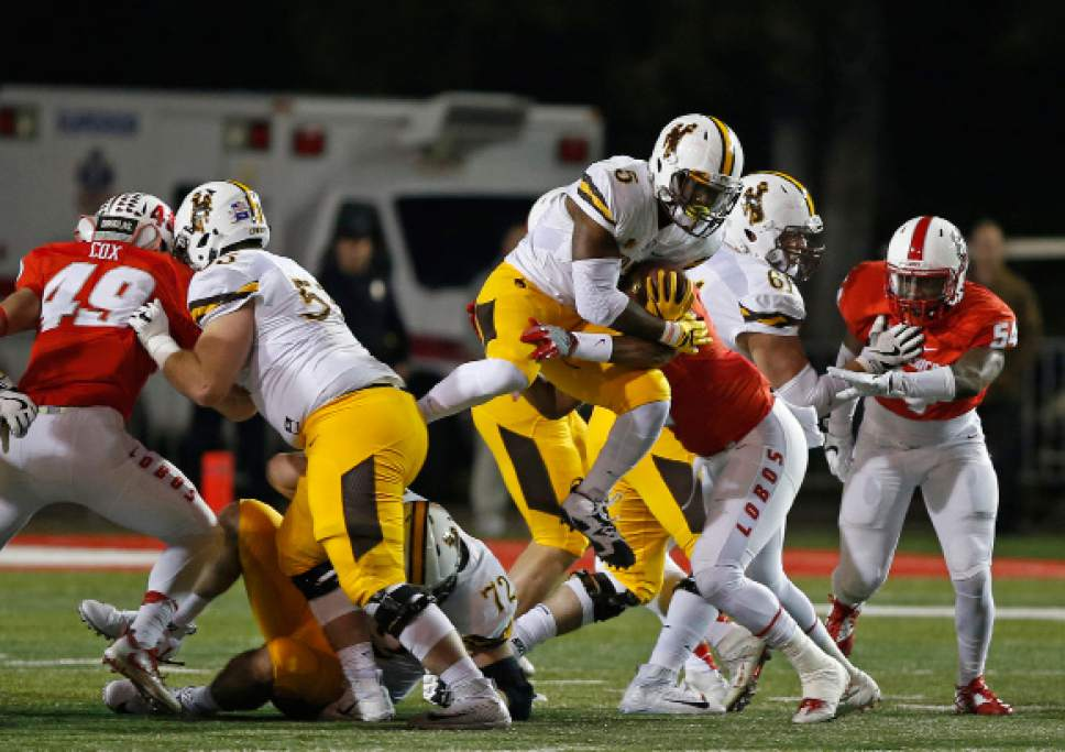 Wyoming running back Brian Hill (5) is stopped by New Mexico linebacker Kimmie Carson, obscured, during the first half of an NCAA college football game in Albuquerque, N.M., Saturday, Nov. 26, 2016. (AP Photo/Andres Leighton)