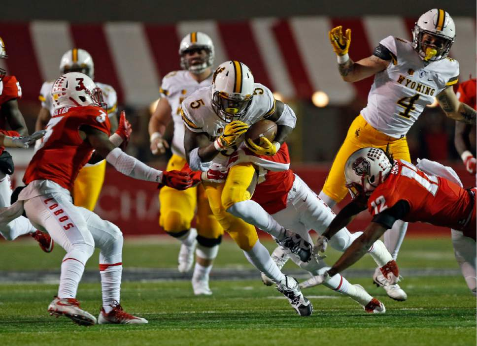 Wyoming running back Brian Hill (5) is sacked by New Mexico safety Daniel Henry, obscured, as New Mexico's Ryan Santos (12) and Nias Martin (3) defends during the first half of an NCAA college football game in Albuquerque, N.M., Saturday, Nov. 26, 2016. (AP Photo/Andres Leighton)