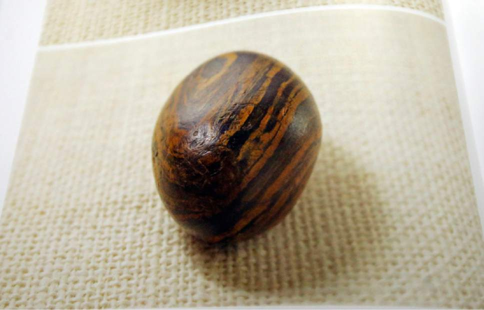 A picture of a smooth, brown, egg-sized rock is shown in the printer's manuscript of the Book of Mormon following a news conference Tuesday, Aug. 4, 2015, at The Church of Jesus Christ of Latter-day Saints Church History Library, in Salt Lake City. The Mormon church for the first time is publishing photos of a small sacred stone it believes founder Joseph Smith used to help translate the story that became the basis of the religion. The Mormon church is taking another step in its push to be more transparent, and is releasing more historical documents that shed light on how Joseph Smith formed the religion. (AP Photo/Rick Bowmer)