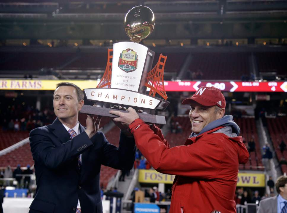 FILE - In this Dec. 26, 2015, file photo, Nebraska coach Mike Riley, right, holds the champions trophy alongside a Foster Farms official after Nebraska's 37-29 win over UCLA during the Foster Farms Bowl NCAA college football game in Santa Clara, Calif. Two people involved in the decision tell The Associated Press that the NCAA won't allow the creation of new bowl games for the next three years. The people spoke on condition of anonymity Monday, April 11, 2016, because the NCAA had not made a formal announcement.(AP Photo/Marcio Jose Sanchez)