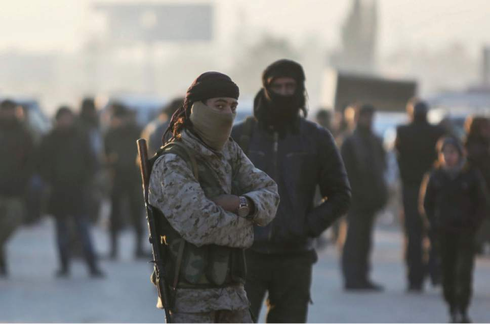 Armed Syrian fighters evacuated from the embattled Syrian city of Aleppo during the ceasefire arrive at a refugee camp in Rashidin, near Idlib, Syria, Tuesday, Dec. 20, 2016. Russian Foreign Minister Sergey Lavrov said on Tuesday that Russia, Iran and Turkey are ready to act as guarantors in a peace deal between the Syrian government and the opposition. He spoke on Tuesday after a meeting of the three countries' foreign ministers in Moscow. (AP Photo)