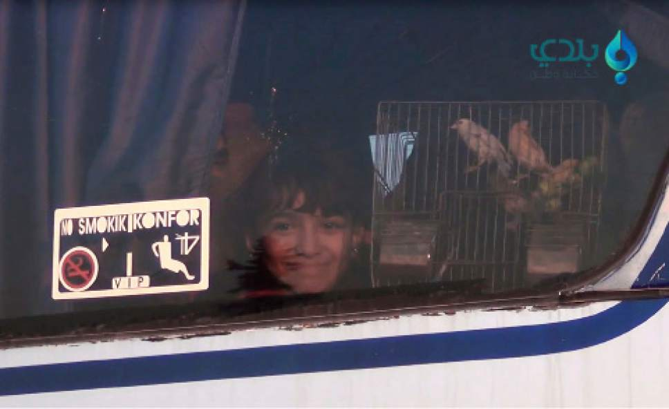 In this still image taken from video released by Baladi News, a Syrian opposition-affiliated media outlet, on Tuesday, Dec. 20, 2016, a girl inside a bus holds up her bird-cage, one of the east Aleppo residents arriving to the city's countryside as part of an evacuation process that commenced last week. The International Committee for the Red Cross said it has overseen the evacuation of 25,000 people from east Aleppo since rebels effectively surrendered the area to the Syrian government. (Baladi News via AP)