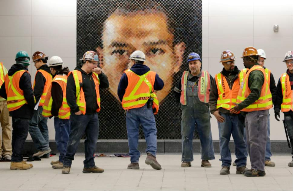 Construction workers stand in front of a mosaic by Chuck Close at the new 86th Street subway station in New York, Thursday, Dec. 22, 2016. The first phase of the 2nd Avenue subway line, which has three stops, is scheduled to open on Jan. 1, 2017. (AP Photo/Seth Wenig)