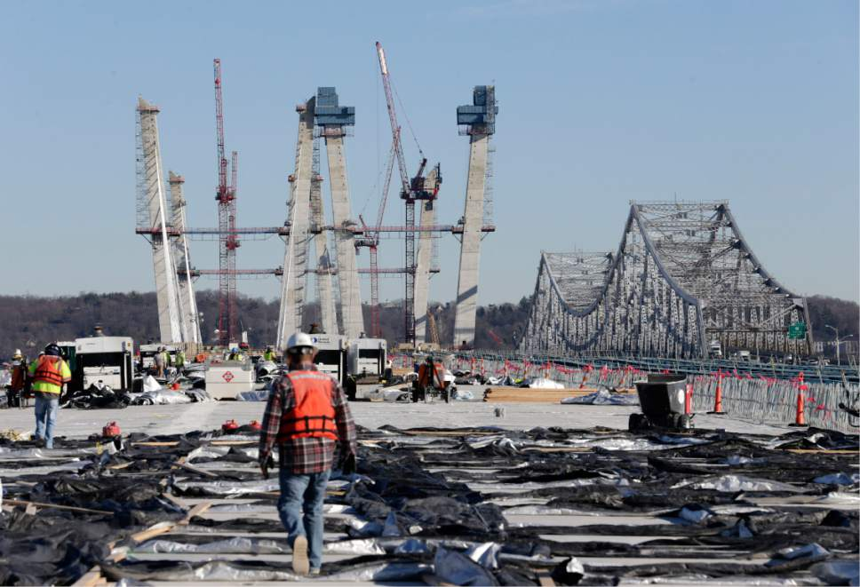 Construction workers walk on the new Tappan Zee Bridge while the old one, right, is still in use near Tarrytown, N.Y., Tuesday, Dec. 20, 2016. Work on the 3-mile bridge began in 2013. (AP Photo/Seth Wenig)