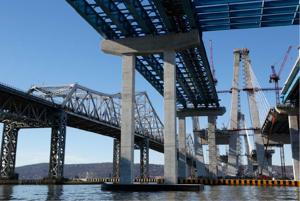 Work continues on the new Tappan Zee Bridge, right, while the older one, left, is still in use near Tarrytown, N.Y., Tuesday, Dec. 20, 2016. New York Gov. Andrew Cuomo said he made replacing the old Tappan Zee a priority because it was disintegrating and eating up hundreds of millions of dollars for basic repairs just to keep motorists safe. (AP Photo/Seth Wenig)