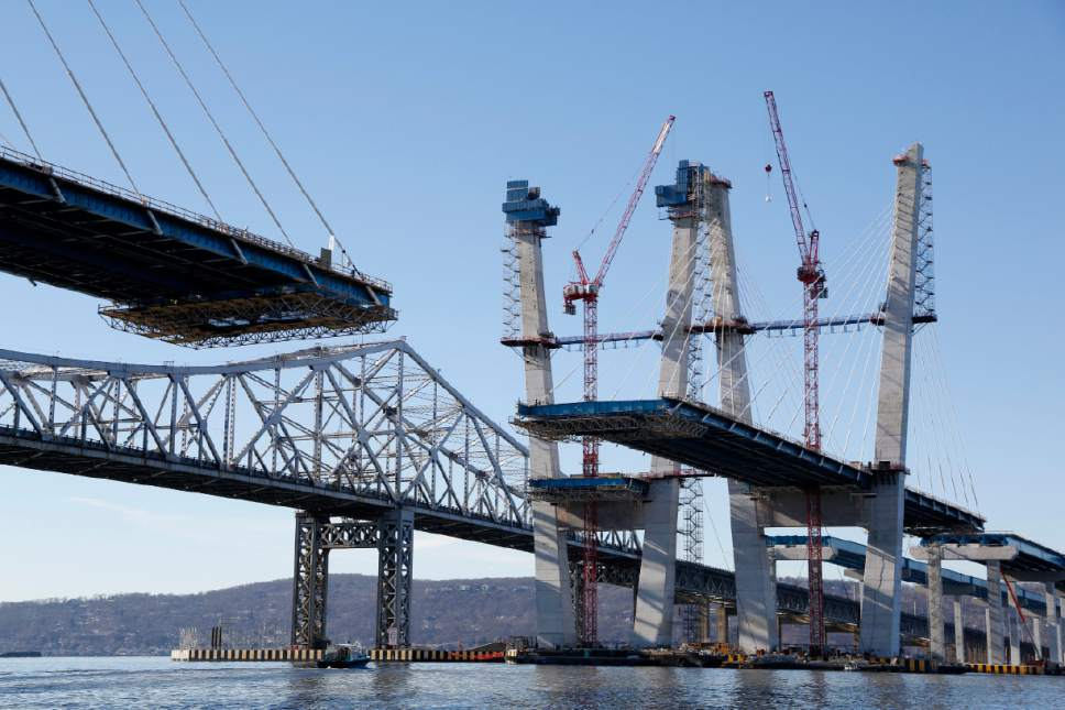 Work continues on the new Tappan Zee Bridge, foreground, while the older one is still in use near Tarrytown, N.Y., Tuesday, Dec. 20, 2016. The new bridge about 25 miles north of New York City stands next to the 61-year-old Tappan Zee that has been falling apart for years. (AP Photo/Seth Wenig)