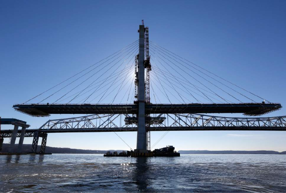 A span on the new Tappan Zee Bridge, foreground, awaits completion while motorists continue to use the older bridge near Tarrytown, N.Y., Tuesday, Dec. 20, 2016. Without the bridge, the next Hudson crossing is 20 miles north and carries a sliver of the traffic volume. The next crossing to the south is through traffic-choked Manhattan, barely visible 25 miles in the distance. (AP Photo/Seth Wenig)
