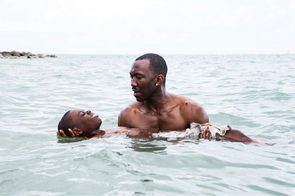 """This image released by A24 Films shows Alex Hibbert, left, and Mahershala Ali in a scene from the film, """"Moonlight.""""  (David Bornfriend/A24 via AP)"""