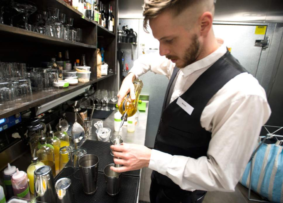 "Steve Griffin | The Salt Lake Tribune   Table X bartender Warren Beecroft mixes a new drink called ""The Last Toddy"" at the new restaurant in Salt Lake City, Wednesday, Dec. 14, 2016. The restaurant has created a twist on the ""hot toddy,"" creating the drink with Beehive Jack Rabbit Gin (made in Utah), green chartreuse, St. Germain (elderflower liquor), lime, rosemary and juniper."