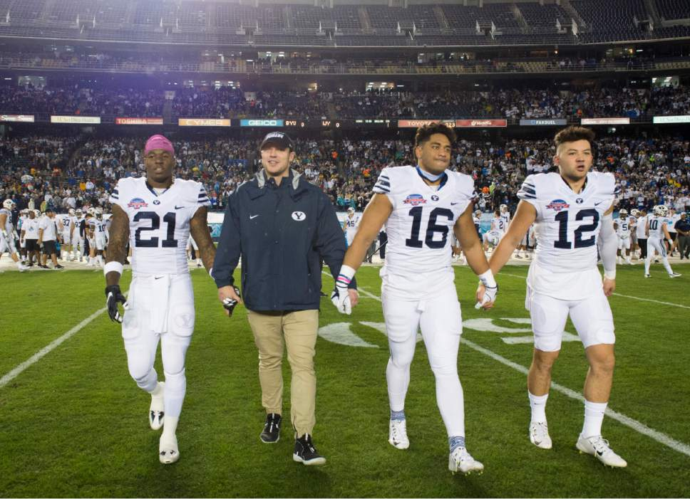 Rick Egan  |  The Salt Lake Tribune  Brigham Young Cougars running back Jamaal Williams (21) quarterback Taysom Hill, linebacker Harvey Langi (16), and quarterback Tanner Mangum (12) enter the field for the coin toss before the start of the Poinsettia Bowl, Brigham Young Cougars vs. Wyoming Cowboys at Qualcomm Stadium in San Diego, December 21, 2016.