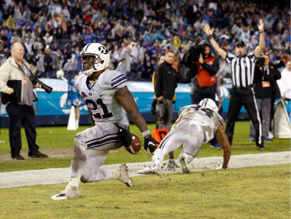 BYU running back Jamaal Williams, left, scores a touchdown against Wyoming during the first half of the Poinsettia Bowl NCAA college football game Wednesday, Dec. 21, 2016, in San Diego. (AP Photo/Ryan Kang)