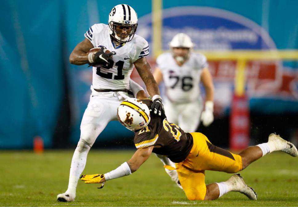 BYU running back Jamaal Williams, left, pushes off roim Wyoming cornerback Antonio Hull, right, during the first half of the Poinsettia Bowl NCAA college football game Wednesday, Dec. 21, 2016, in San Diego. (AP Photo/Ryan Kang)