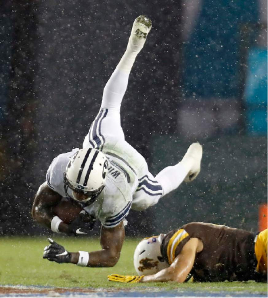 BYU running back Jamaal Williams, left, falls over Wyoming defensive back Marcus Epps, right, during the first half of the Poinsettia Bowl NCAA college football game Wednesday, Dec. 21, 2016, in San Diego. (AP Photo/Ryan Kang)