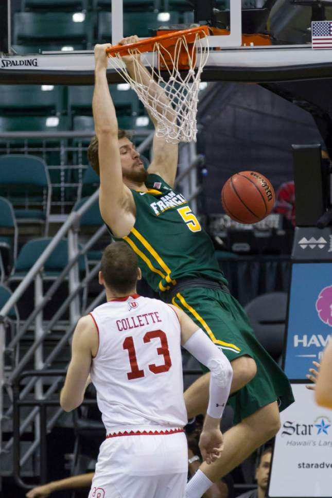 Utah forward David Collette (13) watches as San Francisco center Jimbo Lull (5) dunks during the first half of an NCAA college basketball game at the Diamond Head Classic, Thursday, Dec. 22, 2016, in Honolulu. (AP Photo/Eugene Tanner)