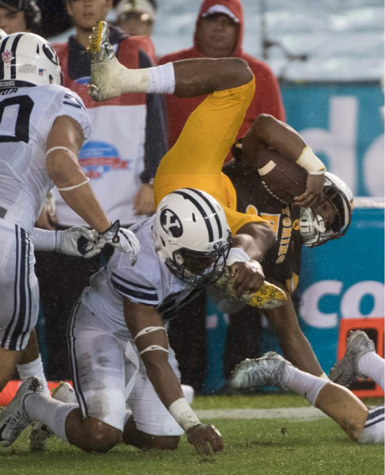 Rick Egan  |  The Salt Lake Tribune  Wyoming Cowboys wide receiver Austin Conway (25) is talked by BYU defenders, uns the ball, in football action, Brigham Young Cougars vs. Wyoming Cowboys at Qualcomm Stadium in San Diego, December 21, 2016.