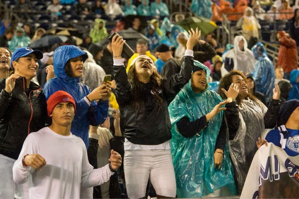 Rick Egan  |  The Salt Lake Tribune  Brigham Young Cougar fans sing and dance in the rain as Brigham Young Cougars lead Wyoming 7-0 in football action, Brigham Young Cougars vs. Wyoming Cowboys in the Poinsettia Bowl, at Qualcomm Stadium in San Diego, December 21, 2016.