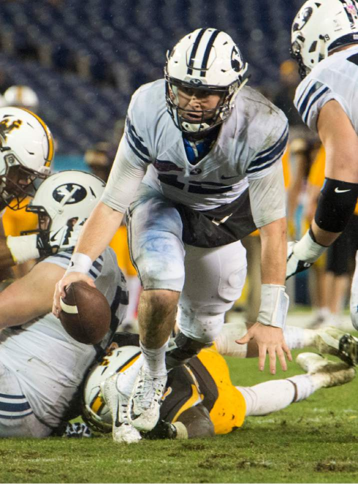 Rick Egan  |  The Salt Lake Tribune  Brigham Young quarterback Tanner Mangum (12) scrambles before throwing a touchdown pass for the Cougars, in football action, Brigham Young Cougars vs. Wyoming Cowboys in the Poinsettia Bowl, at Qualcomm Stadium in San Diego, December 21, 2016.